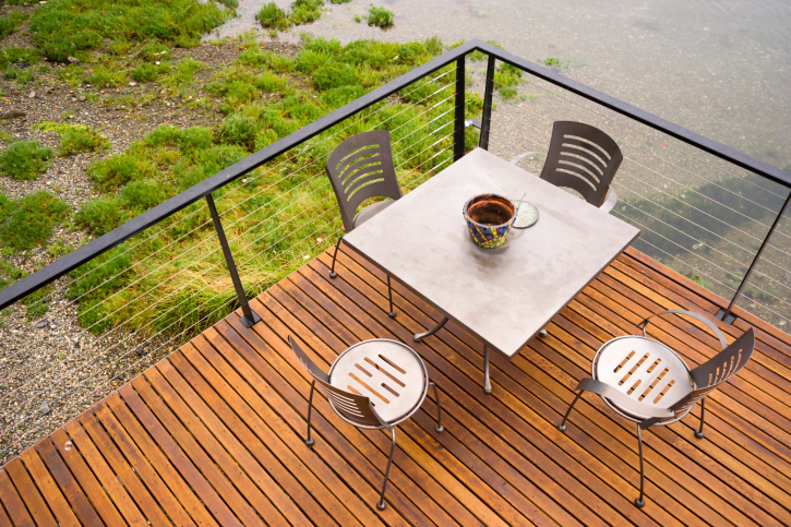 Simple wooden deck with metal railing and metal furniture