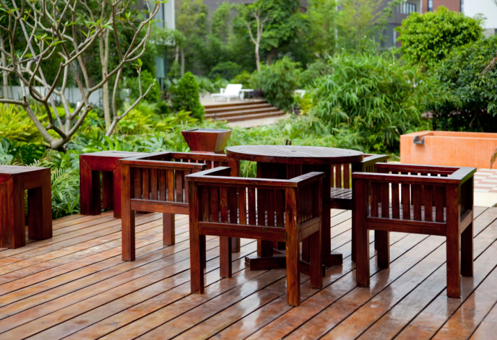 Large stained wooden deck with no railing and matching wood deck furniture