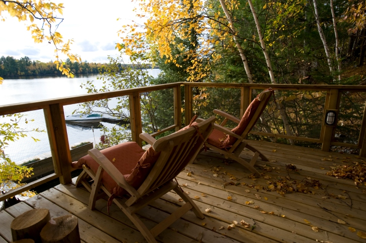 Simple deck and railing overlooking lake with Adirondack chairs
