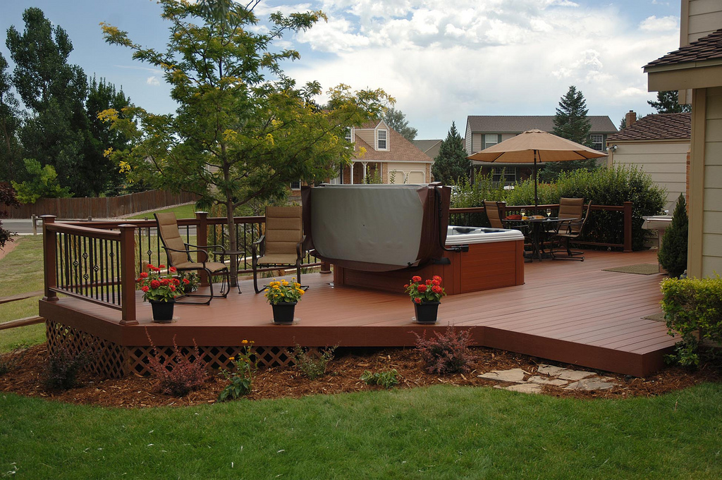 Multi-sided wood deck with hot tub and dining table