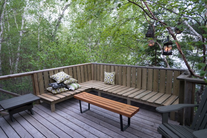 Elevated deck amid trees with built-in bench