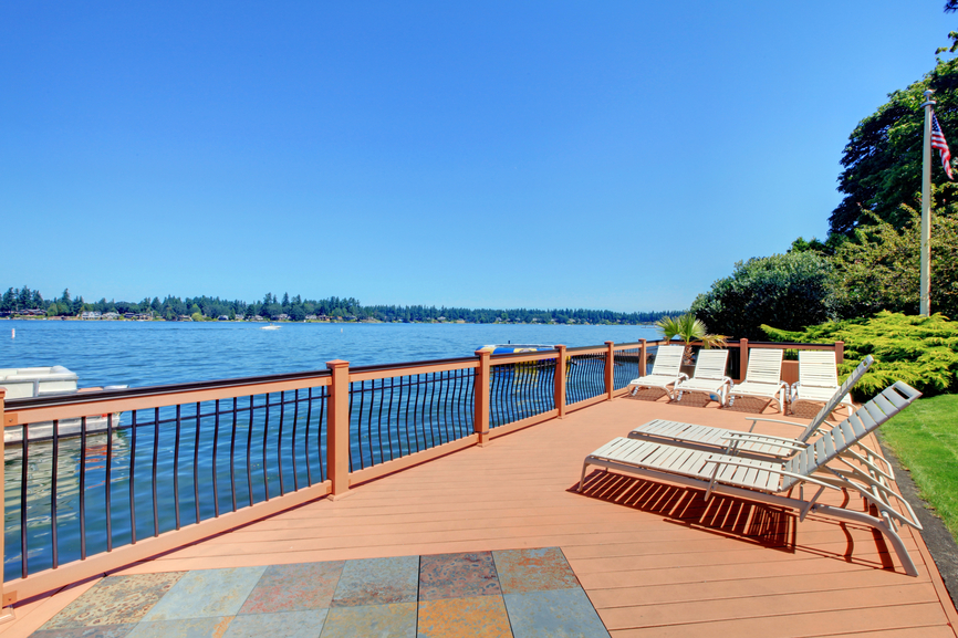 Large waterfront wood deck with wood and iron railing