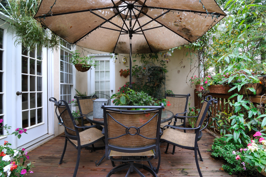 Cozy wooden deck with table and chairs and plenty of plants