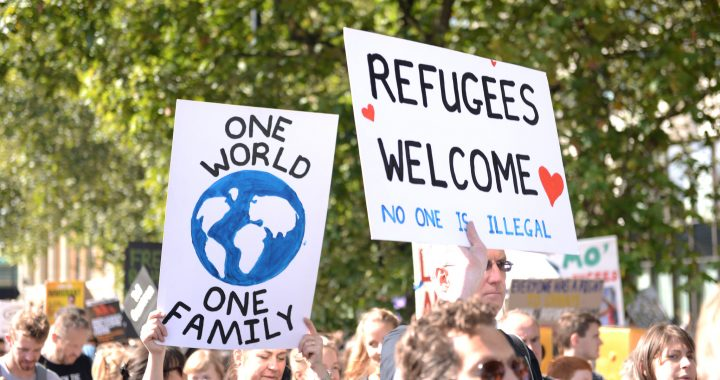 "Crowd with signs saying ""One World, One Family"" and ""Refugees Welcome: No One Is Illegal"". Credit: Ilias Bartolini, Flickr"