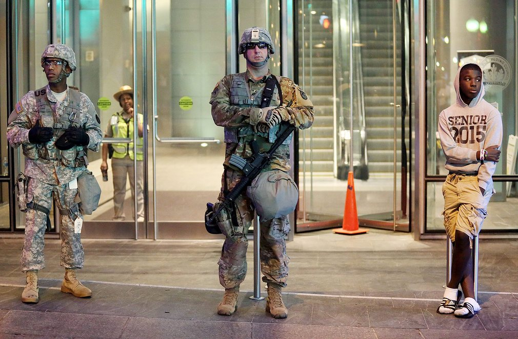 A boy stands next to members of the North Carolina National Guard in downtown Charlotte Photograph: Veasey ConwayEPA