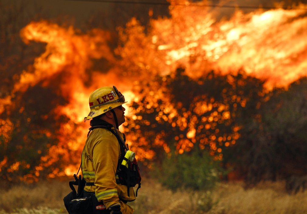 Lakeside firefighter Joe Vasquez watches as large flames burn next to a home on Highway 94  Photograph: Hayne Palmour IVAP