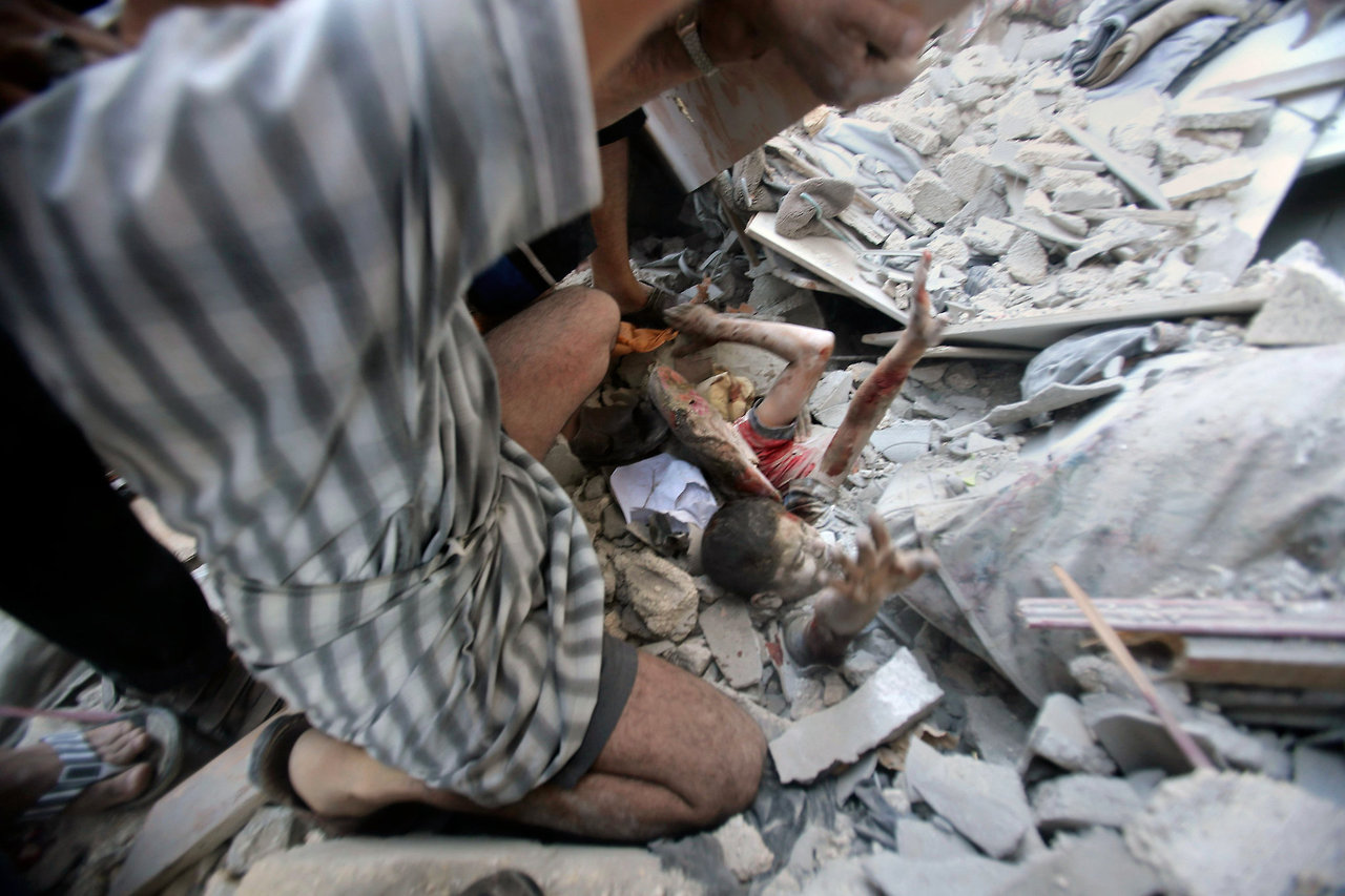 A wounded Palestinian boy calls for help as rescuers pull him from the rubble of a house owned by the al-Ghol family that was destroyed in an Israeli air strike in Rafah
