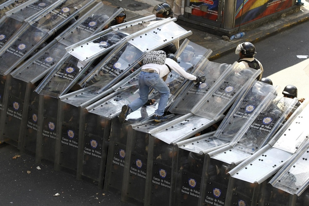 A demonstrator jumps on a wall of shields formed by the riot police