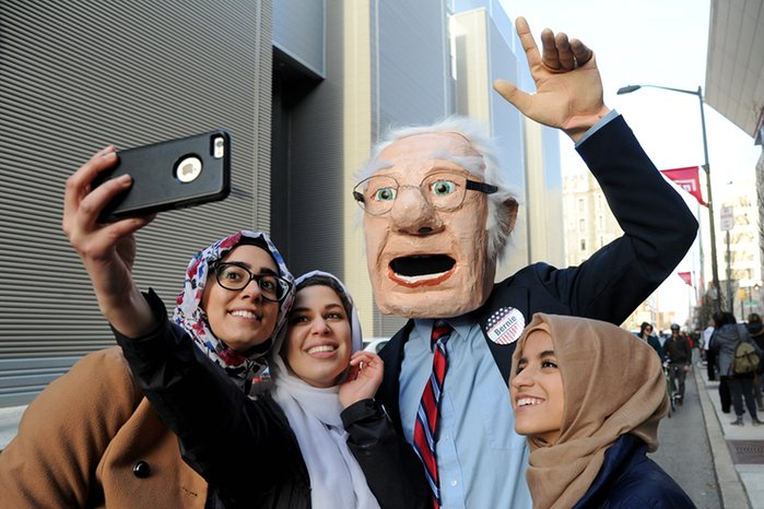 A man in an oversized Bernie Sanders head poses for a selfie with students waiting to see the Democratic presidential hopeful Photograph: Tom GralishAP