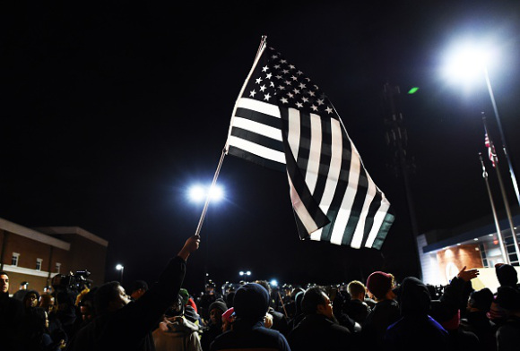 "A protester waves a ""black and white"" modified US flag during a march following the grand jury decision in the death of 18-year-old Michael Brown in Ferguson"