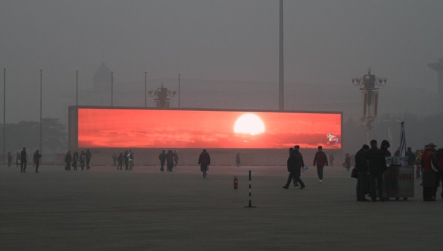 An LED screen shows the rising sun on the Tiananmen Square which is shrouded with heavy smog on January 16, 2014 in Beijing, China