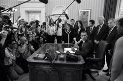 Press members photograph President Obama signing the student loan bill