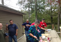 Mission team members from Ginghamsburg United Methodist Church take a break from construction work for an important event: celebrating the birthday of the widowed homeowner.