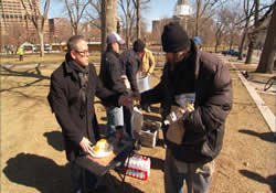 The Rev. Jerry Herships (left) serves Communion and shares sandwiches in ministry with the hungry and homeless as part of the outreach of AfterHours Denver, a young United Methodist congregation.