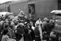 Japanese Americans going to internment camp Manzanar in Owens Valley gather around a baggage car at the old Santa Fe Station in Los Angeles, California, April 1942. Manzanar was one of 10 camps in the United States where over 110,000 Japanese Americans were forcibly removed (incarcerated) during World War II between December 1942 to 1945. Photo from United States Library of Congress' Prints and Photographs division, I.D. fsa. 8a31149, by Russell Lee, courtesy of Wikimedia Commons.