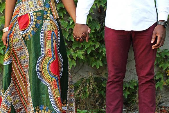 African-American couple holding hands in front of vine-covered wall. Image by Vanessa Pla, Pixabay.com.