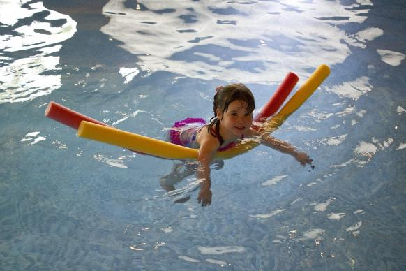 A girl floats on pool noodles in a swimming pool. Image by Sally Wynn, Pixabay.com. CC0 Public Domain.