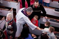 The Rev. Mel Kawakami, center, greets children after church. The pastor, church members say, is able to help ease difficult situations through his self-deprecating humor. Courtesy of Newtown United Methodist Church.