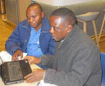 Dr. Alexis Ngoy Kasole Maloba (left), United Methodist Church health coordinator in Democratic Republic of Congo, and Dr. Philippe Okonda Akasa, health coordinator for East Congo, examine data on malaria at Alliance for Malaria Prevention Conference in Geneva. Photo by Gary Henderson, United Methodist Communications.