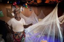 Matilda Ndanema displays the insecticide-treated mosquito net she received from the United Methodist Church's Imagine No Malaria campaign at her home in Bumpe, Sierra Leone. Photo by Mike DuBose, UMNS.