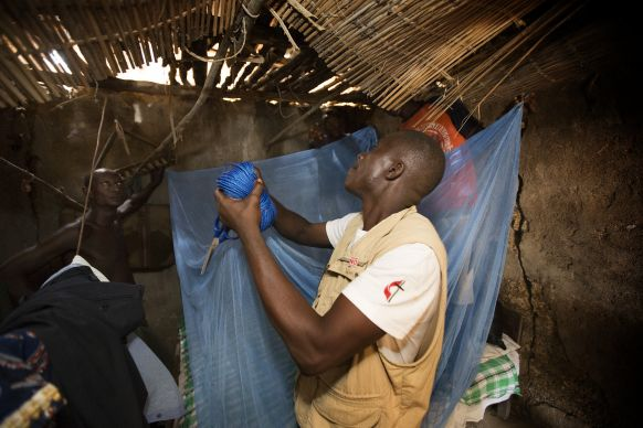 Ernest Jusu, a nurse working with The United Methodist Church's Imagine No Malaria campaign, helps hang a new, insecticide-treated mosquito net at the home of Peter Braima in Manjama, near Bo, Sierra Leone. Photo by Mike DuBose, UMNS
