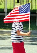 A child holds the American flag during an Independence Day celebration. Photo by E.D.W.W., Wikimedia Commons.