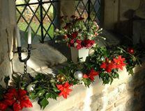 Christmas decorations, Throckmorton Church (Worcestershire, England) Christmas decorations on a window sill beside a stone corbel in Throckmorton church. Photo by Phillip Halling, courtesy Wikimedia Commons.