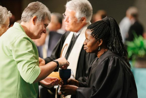 The Rev. Tonya Elmore takes communion from the Rev. Virginia Kagoro. Holy Communion was part of the Service of Remembrance at the 215 Alabama-West Florida Conference on June 1. Photo by Luke Lucas, Alabama-West Florida Conference.