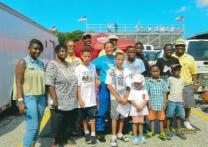 Professional driver Geneva Williams poses with Fast Track 2 Success students during their visit to a hot rod race track. Photo courtesy Grace Community United Methodist Church, Chester, Pennsylvania.