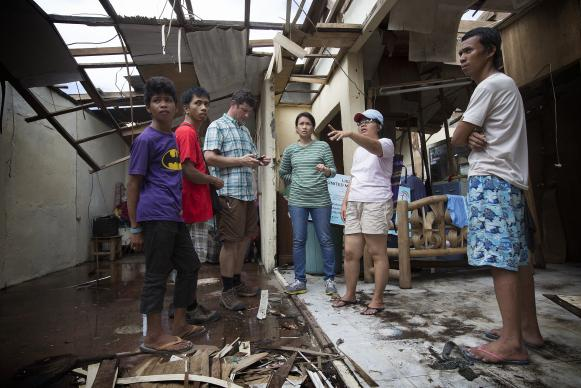Pastor Iris Picardal Terana (second from right) describes damage from Typhoon Haiyan at Light and Life United Methodist Church in Tacloban, Philippines for a visiting technology team from United Methodist Communications and Inveneo. From left are: church member Ronell de Juan; Ernani Celzo, working with UMCom; Clark Ritchie of Inveneo, April Gonzaga-Mercado, working with UMCom; Terana; and her husband Jhonril Terana. 2013 photo by Mike DuBose, UMNS.