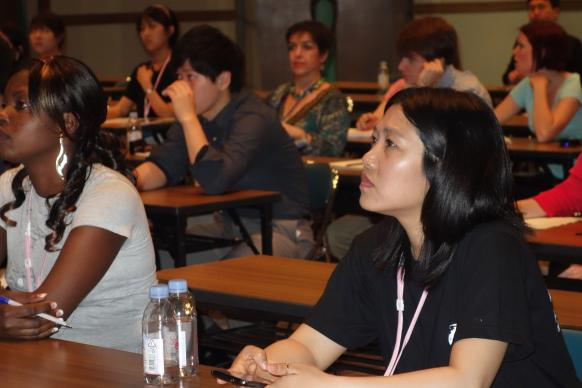 Esther Ojong Ntui of Cameroon, a student at Africa University, and Daphy Nataloo, Myanmar, Yonsei University, listen to a presentation by Courtney Lawrence, who teaches global studies at Hiroshima Jogakuin University. Photo by Diane Degnan, United Methodist Communications.