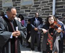 The Rev. Kevin Slayton, left, prays outside New Waverly United Methodist Church after death of Freddie Gray. Photo by Melissa Lauber, courtesy of the Baltimore-Washington Conference.