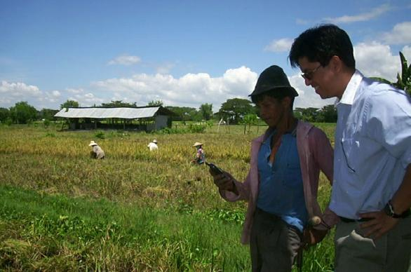 Two men in a rural area of the Philippines check a mobile phone. Photo by Ken Banks, kiwanja.net.