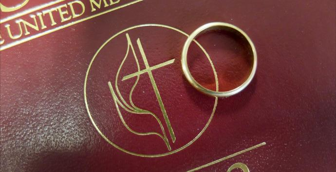 A wedding band rests on the Cross and Flame insignia of the 2012 Book of Discipline. United Methodist bishops seek to offer clarity after the U.S. Supreme Court ruled same-sex marriage legal across the United States. Photo illustration by Kathleen Barry, United Methodist Communications.