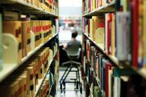 Student sits in library amid books. Image courtesy of UMC Giving.