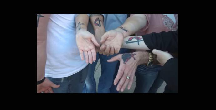 People show their Cross and Flame and other faith tattoos. Video image by Reed Galin, courtesy of United Methodist Communications.