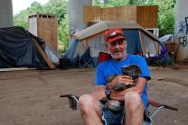 Resident of tent city in Greenville, South Carolina with puppy. Photo by Jessica Connor, the South Carolina Advocate.