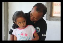 Roger Modesta and his five year old daughter, Lorraine, sit in their new house, made possible through the UMCOR rebuilding project. Their home in Calogcog, a barangay (community) of the Philippine municipality of Tanauan in Leyte Province, was destroyed by Typhoon Haiyan in November 2013. Photo by Melissa Hinnen, UMCOR.