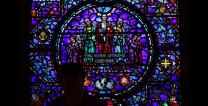 A woman stands silhouetted against a stained-glass window outside The Upper Room chapel.  Photo by Kathleen Barry, UMNS.