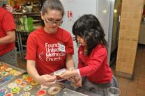 Vanessa Smiley helps Jules, 4, bag cookies for delivery with meals to two neighboring social service agencies to feed to their clients.