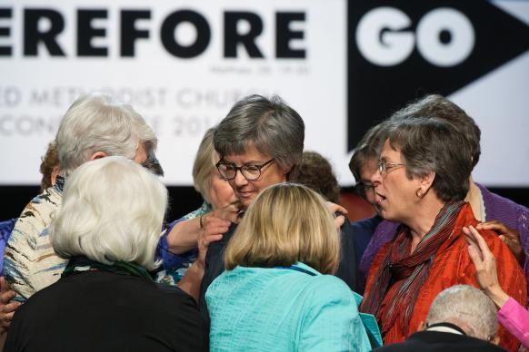 Bishops pray for one another. Several bishops prayed for North Carolina Bishop Hope Morgan Ward (center) after she finished presiding over a session of General Conference. #GCUMC Photo by Mike DuBose, United Methodist Communications.