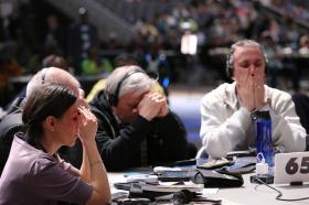 Delegates pray around their tables.