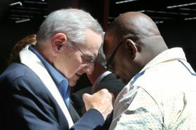 Bishop Goodpaster prays with someone during break.