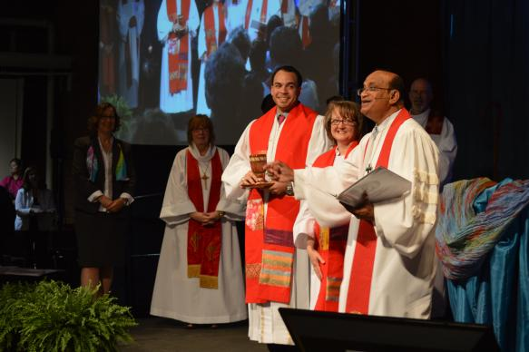 Following their ordination, the first thing many new clergy do is serve communion, as Jeffrey Luis Hooker and Janet Elmas Deranian assisted Bishop Sudarshana Devadhar at 2015 New England Annual Conference. Photo by Beth DiCocco, New England Conference.