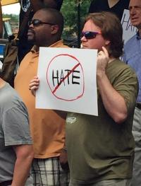 Protester holds up a sign that reads, no hate.