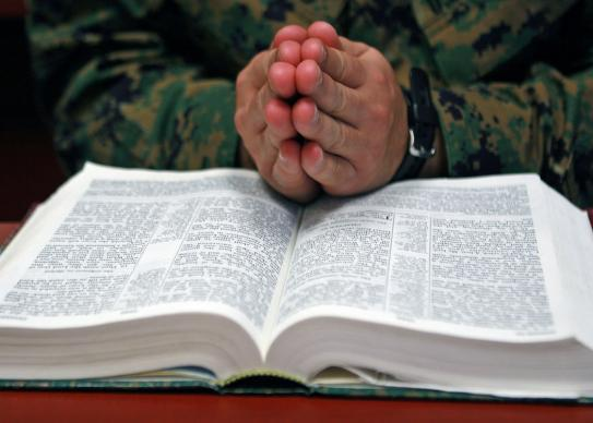Hands in prayer over a Bible. Photo by Lance Cpl. Austin Goacher, courtesy of Wikimedia Commons.
