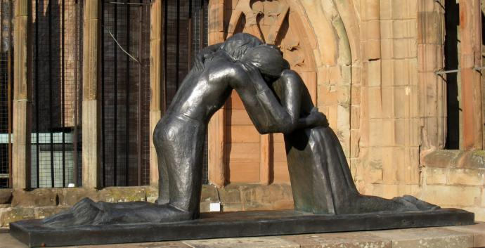 Two former enemies embrace in Vasconcellos' sculpture Reconciliation. Photo by Martinvl, courtesy Wikimedia Commons.