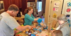 A group works together to makes sandwiches for those in need.