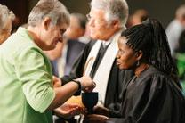 The Rev. Tonya Elmore, pastor at Enterprise First United Methodist Church, takes communion from the Rev. Virginia Kagoro, pastor at Locust Bluff United Methodist Church. Holy Communion was part of the Service of Remembrance at the 2015 Alabama-West Florida Conference on June 1, where 33 clergy and clergy spouses were memorialized. Photo by Luke Lucas, Alabama-West Florida Conference