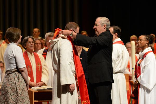 Rev. Jon Van Dop receives stole from mentor at ordination.